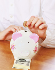 Young beautiful woman with piggy bank (money box), isolated on