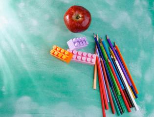 Red apple, pencils, construction set