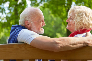 Paar Senioren beim Kennenlernen auf Bank im Park
