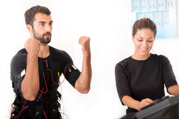 Female coach giving man ems electro muscular stimulation exercis