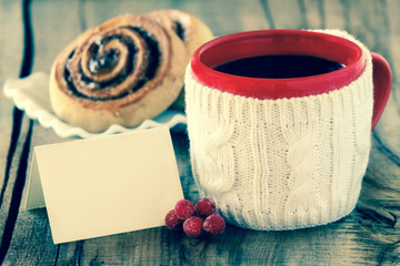Christmas setting - red mug of black coffee and a greeting card