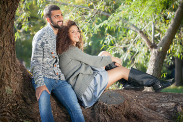 happy young couple leaning against a tree enjoying the autumn in