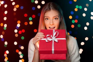 Happy girl opening Christmas box which is glowing inside. Gift