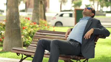 Young businessman relaxing and enjoying day sitting on bench in