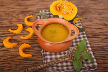 Pumpkin soup in clay pot with fresh pumpkins for healthy
