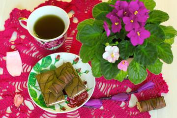 чаепитие со сладостями на фоне фиолетовых фиалок