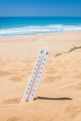 Heat time to come on vacation to beach. Thermometer on beach.