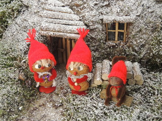 Christmas card - gnomes in front of their cosy home in the fores