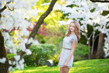 Beautiful young girl in cherry garden