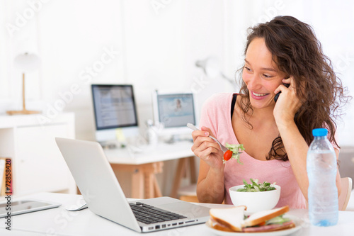 canvas print picture Young attractive student eating salad while phoning