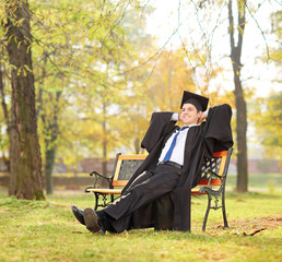 Relaxed graduate student sitting on a bench in park