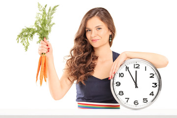 Woman holding a bunch of carrots and a big wall clock