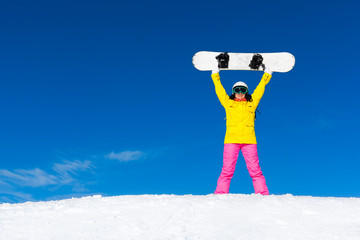 snowboarder girl raised arms standing hold snowboard