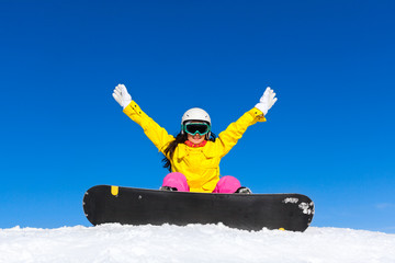 snowboarder woman sitting on snow mountain slope happy raised
