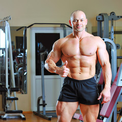 Bodybuilder showing thumbs up in gym