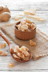 Ginger fresh root, ginger candy pieces  on a wooden table