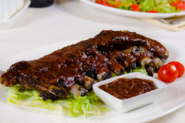 Rack of Saucy Barbecue Pork Ribs on White Plate