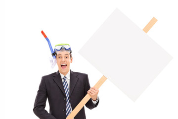 Businessman with diving mask holding blank signboard