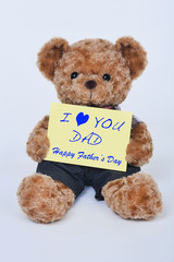 Teddy bear holding a yellow sign that says I love dad