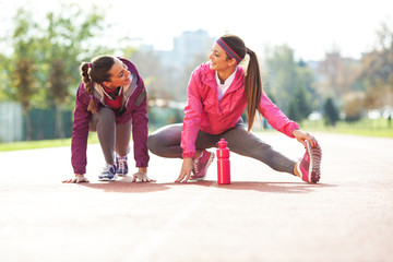 Two attractive female exercising  outdoor.Stretching.