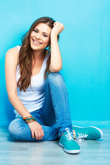 beautifull smiling woman sitting on floor against blue wall