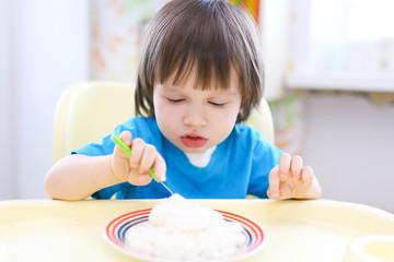 lovely toddler boy eating quark  with sour cream