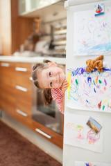 Cute little girl smiling behind refrigerator door in kitchen