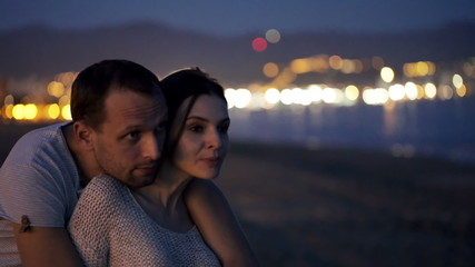 Couple in love hug and talking on beach at night