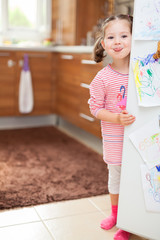 Cute little girl sticking tongue out behind refrigerator door in