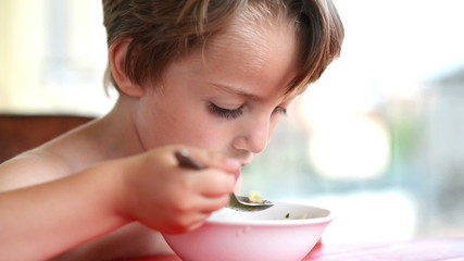 Little Boy learning to eat soup