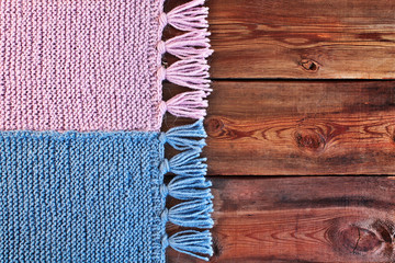 Beautiful knitted scarf on wooden texture