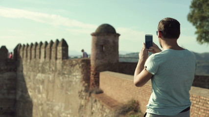 Tourist taking photo of ancient castle ruins with cellphone
