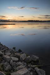 Sunrise vibrant landscape of jetty on calm lake