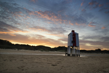Sunrise landscape of wooden stilt lighthouse on beach in Summer