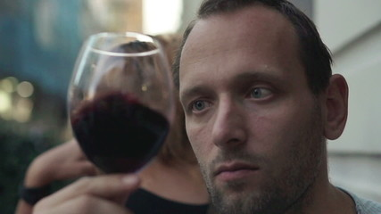 Sad, unhappy man looking at glass of red wine, slow motion, 120f