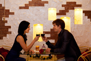 Young happy couple romantic date drink glass of red wine at