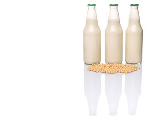 Soybean and bottles of soybean milk over white background