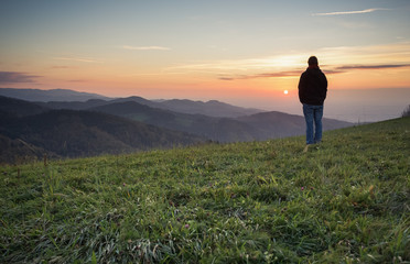 man standing on hill in black forest at sunset