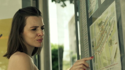 Woman at bus stop looking at map and bus timetable