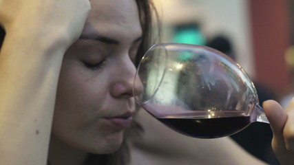 Close up of drunk woman drinking red wine in bar