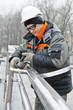 worker polishing metal fence barrier