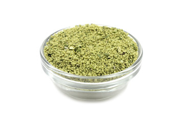 granulated seasoning in a glass container on a white background