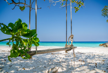 Wood swing on the colorful beach with blue sky