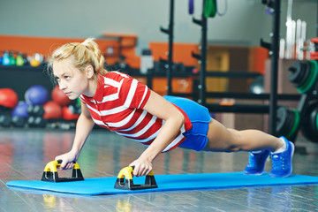 woman pushing up in fitness gym