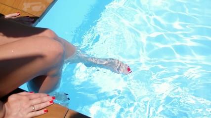 Sexy Woman Legs Splashing in Tropical Swimming Pool. Slow Motion