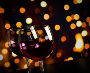 two red wine glasses on wood table on bokeh lights background