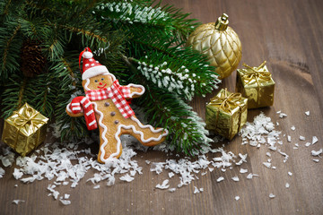 gingerbread man in the snow, fir branches and decorations