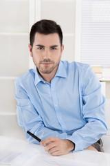 Junger Geschäftsmann sitzend im Büro in Hemd blau