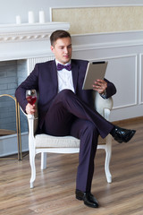 Man resting on the tablet and wine