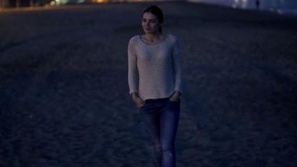 Pretty, happy woman walking on beach at night